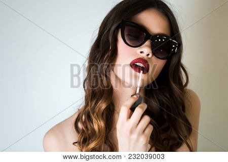 Beautiful Woman In Sunglasses Makes Makeup Applying Red Lipstick On Lips Over White Background