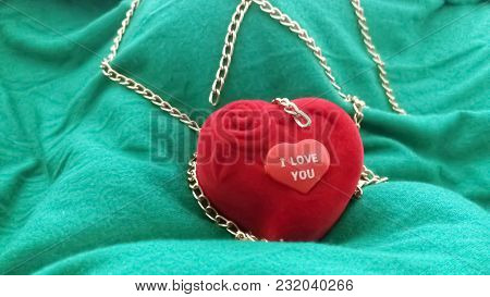 Red Ring Box And An Inscribed Red Love Heart With A Golden Chain On A Green Surface