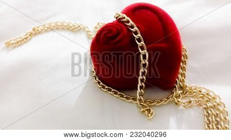 A Red Ring Box Shaped Like A Heart With A Golden Chain On And Around It