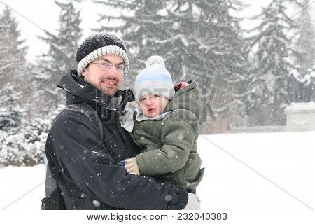 Portrait Of An Young Father, Carrying His Offspring In A Cold Winter Day.