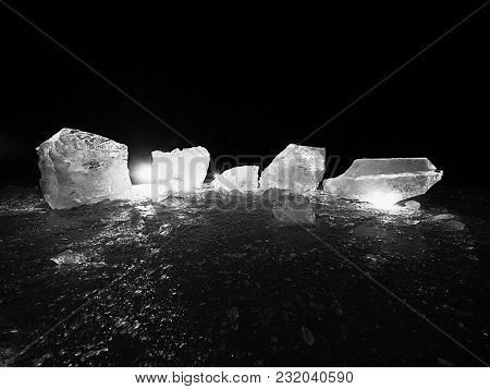 Ice Cubes On A Dark Reflective Ground.  Glowing Pieces Of Chopped Ice And Snowflakes In Strong Backl