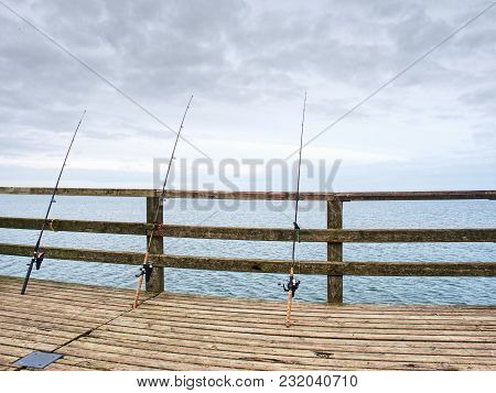 Fishing On Sea Bridge. Fishers Rods Against The Wooden Handrail Of The Beach Mole. Overcast Day, Wit