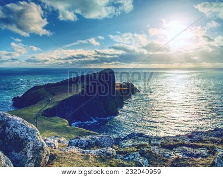 The Neist Point Lighthouse On The End Of  World. Foamy Blue Sea Strikes Against The Sharp Cliff.  Th