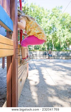 Girl Climbing Steps In Playground And Mother Watching