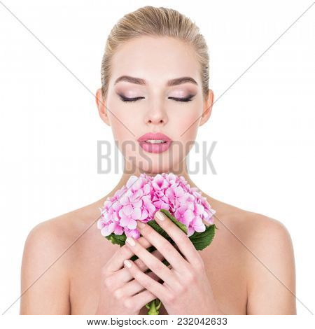 Young beautiful woman with flowers near face. Beauty treatment concept. Skin care. Pretty female with health, fresh skin of body. Lady with pink makeup of eyes.