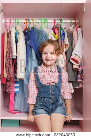 A Little Girl Is Sitting In A Closet With A Children's Department. Storage System For Children's Thi