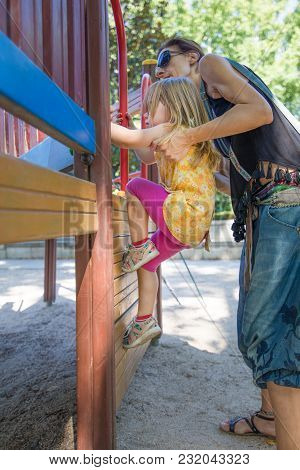 Mother Helping Girl To Climb Steps In Playground