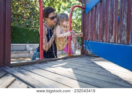 Mother Helping Girl To Climb To The Playground