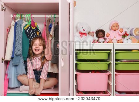A Little Girl Is Sitting In A Closet With A Children's Departmen