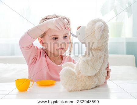Cute little girl feeding toy teddy bear