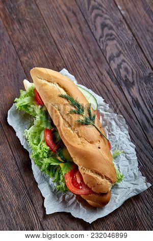 Fresh And Tasty Submarine Sandwich With Cheese, Lettuce And Vegetables On Paper Napkin Over Vintage