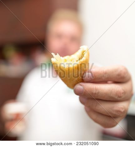 A Man Holds A Patty In His Hand .