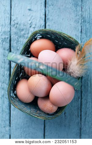 Easter Eggs In Blue Basket On A Wooden Background