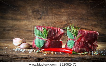 Raw beef fillet steaks mignon with spices on wooden background