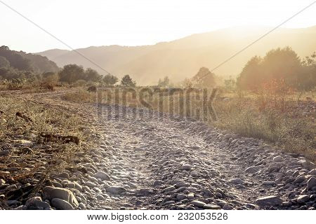 The Horizontal Shot Of Stone Dusty Road In A Dry Valley On A Background Of Bushes And Mountains. Ton