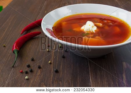 A Bowl Of Borsch With Sour Cream. Spices And Chili Pepper Are Spilled Around The Plate