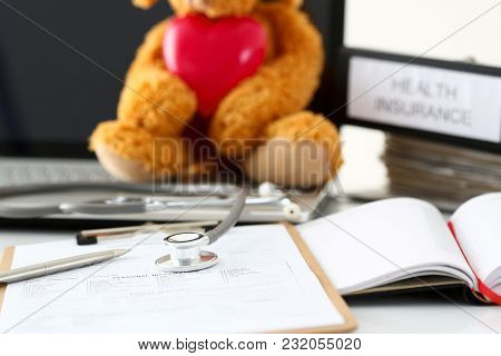 Silver Pen And Phonendoscope Head Lying At Patient History List Closeup And Teddy Bear Holding Toy R