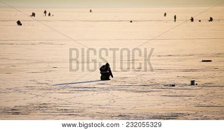 A Man On Ice Is Fishing In The Evening .