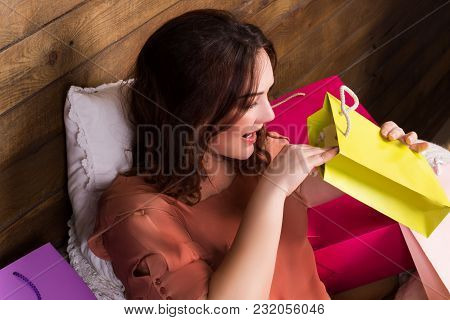 Happy Woman After Shopping With Multcoloured Paper Bags On Bed