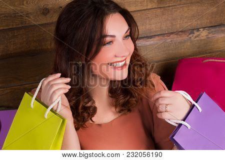 Woman After Shopping With Colourful Paper Bags Near Wooden Wall