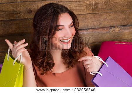 Woman After Shopping With Multicolored Paper Bags Near Wooden Wall