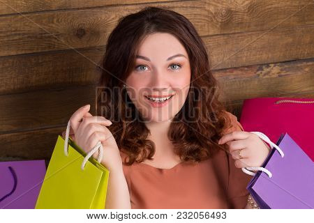 Woman After Shopping With Multicoloured Paper Bags Near Wooden Wall