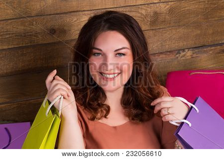 Woman After Shopping With Versicoloured Paper Bags Near Wooden Wall
