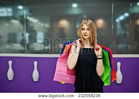 Girl With Shopping Bags In The Mall Against Bowling Club Wall.