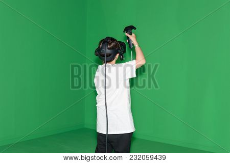 Cologne, Germany - August 24, 2017: A Boy Is Playing A Virtual Reality Game In Front Of A Green Wall
