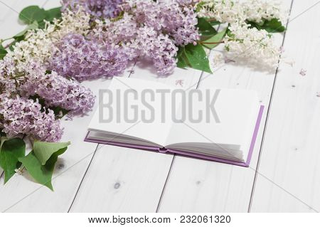 Beautiful White And Violet Lilac Flowers With Opened Note-book On The White Wooden Background, Mock