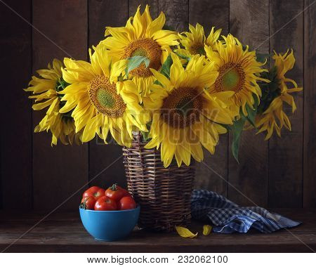 Sunflowers In A Basket And Tomatoes On The Table. Rural Still Life.