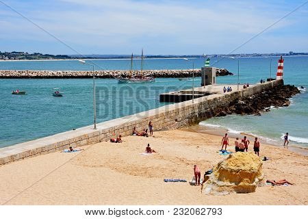 Lagos, Portugal - June 9, 2017 - Tourists Relaxing On Praia Da Batata Beach With Holidaymakers On Bo