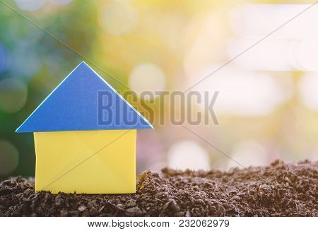 Paper House Origami On Soil Against Blurred Green Natural Background With Copy Space For Residence A