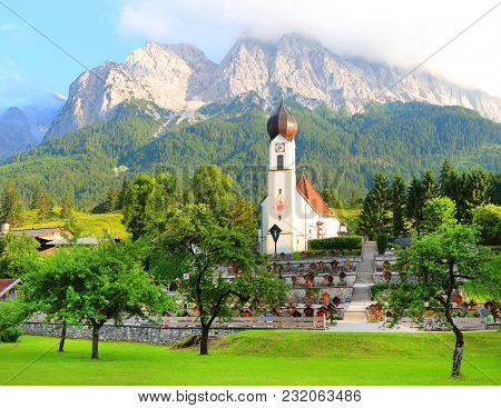 GARMISCH-PARTENKIRCHEN / GERMANY - JULY 4, 2017: View of Grainau's church with the Zugspitze behind.  It is Germany's highest peak (2962 m).