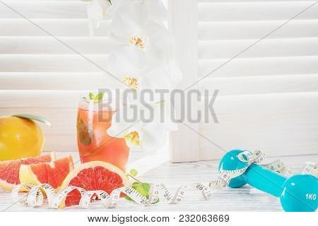 Fresh Red Grapefruits And Grapefruit Juice, Dumbbell And Measuring Tape, On Rustic White Wooden Tabl