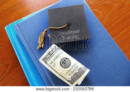 Vocational Training Graduation Cap On A Pile Of Books With Cash -- Certificate Or Junior Two Year De