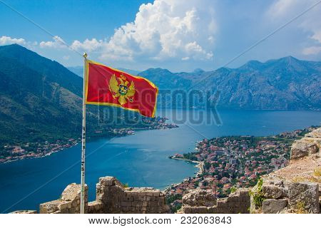 Beautiful View From Above On The Kotor And Bay Of Kotor, Montenegro. Waving In The Wind Flag Of Mont