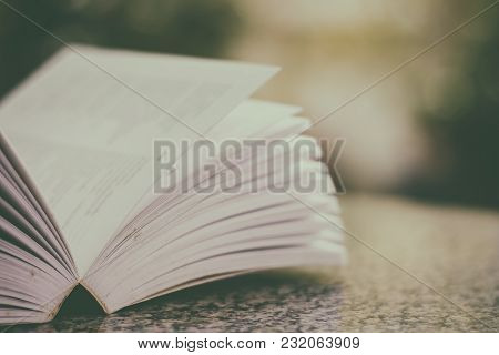 Selective Focus Of Opened Book On Blurred Natural Green Background With Shallow Depth Of Field, Adde