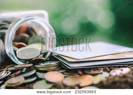 Coin In The Glass Jar And Credit Card On Soil Against Blurred Natural Green Background With Copy Spa