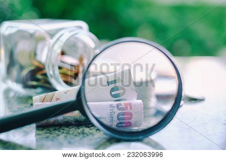 Thai Baht Currency Banknote Zoomed By Magnifying Glass With Blurred The Glass Jar Of Coin Against Na