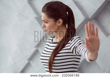 Thoughtful Mood. Serious Pleasant Young Woman Holding Her Hand In Front Of Her And Looking Aside Whi