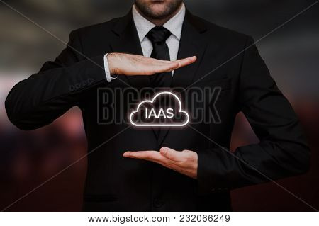 Infrastructure As A Service (iaas) Concept Text In Cloud Between Hands Of The Businessman, Blurry Bo