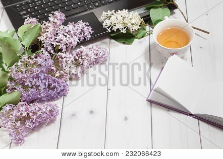 Beautiful Branch Of White And Violet Lilac Flowers With Opened Pad And Black Opened Laptop, Lying On
