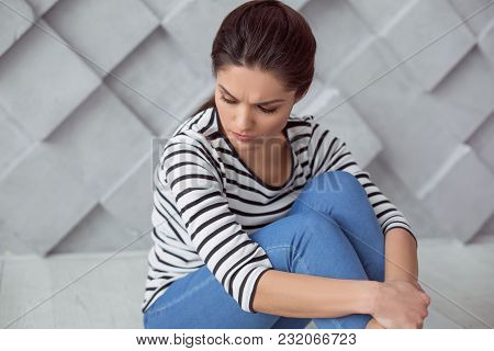 Bad Thoughts. Depressed Cheerless Young Woman Sitting On The Floor And Thinking About Her Life While