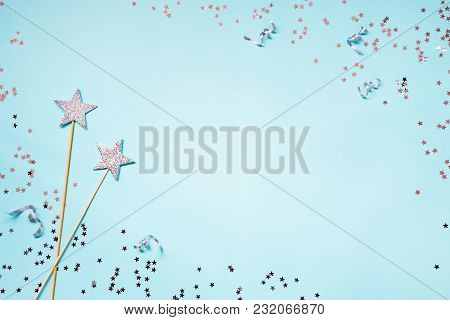 Two Silver Party Magic Wands, Sequins And Ribbons On A Blue Background. Copy Space.