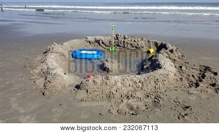 Sandcastle Fort Beside The Atlantic Ocean Coast With Toy Shovel, Blue Float Toy And Yellow Cup, Sand