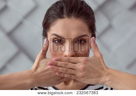Be Silent. Portrait Of A Sad Cheerless Young Woman Covering Her Mouth While Being Silent