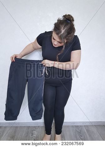 full woman tries on too small pants