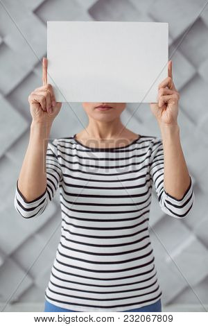 Not To Violence. Sad Depressed Young Woman Standing Against The Wall And Holding A Sheet Of Paper Wh