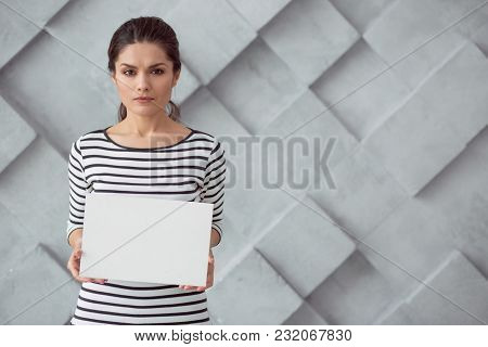 Stop This. Sad Cheerless Young Woman Holding A Sheet Of Paper And Addressing To You While Standing A